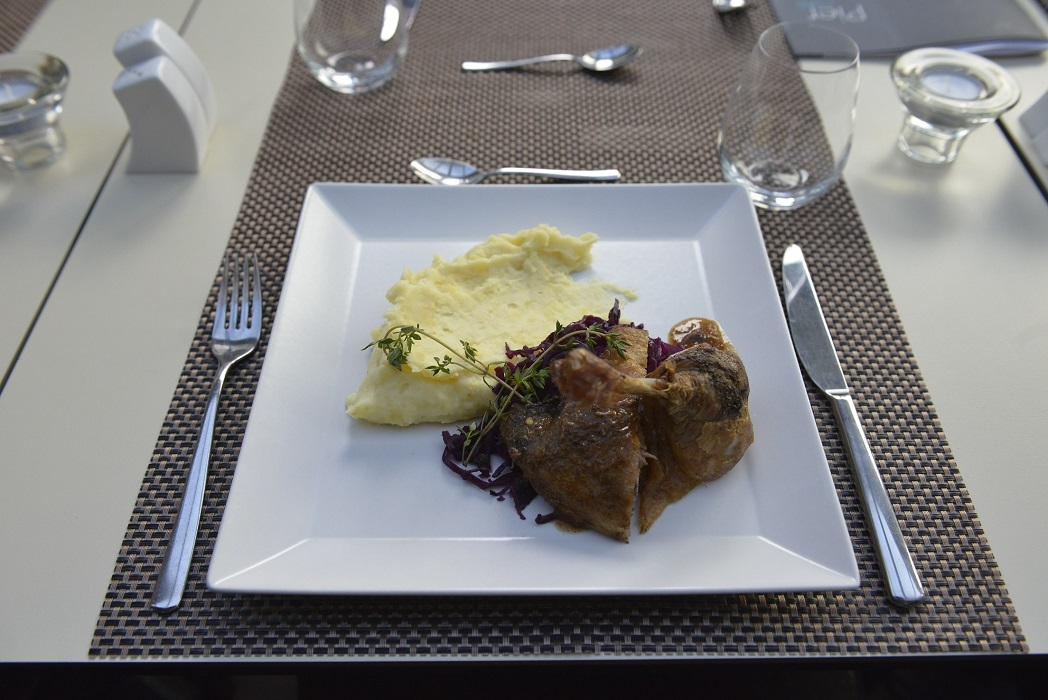 Duck leg confit with buttery mashed potato served with steamed red cabbage